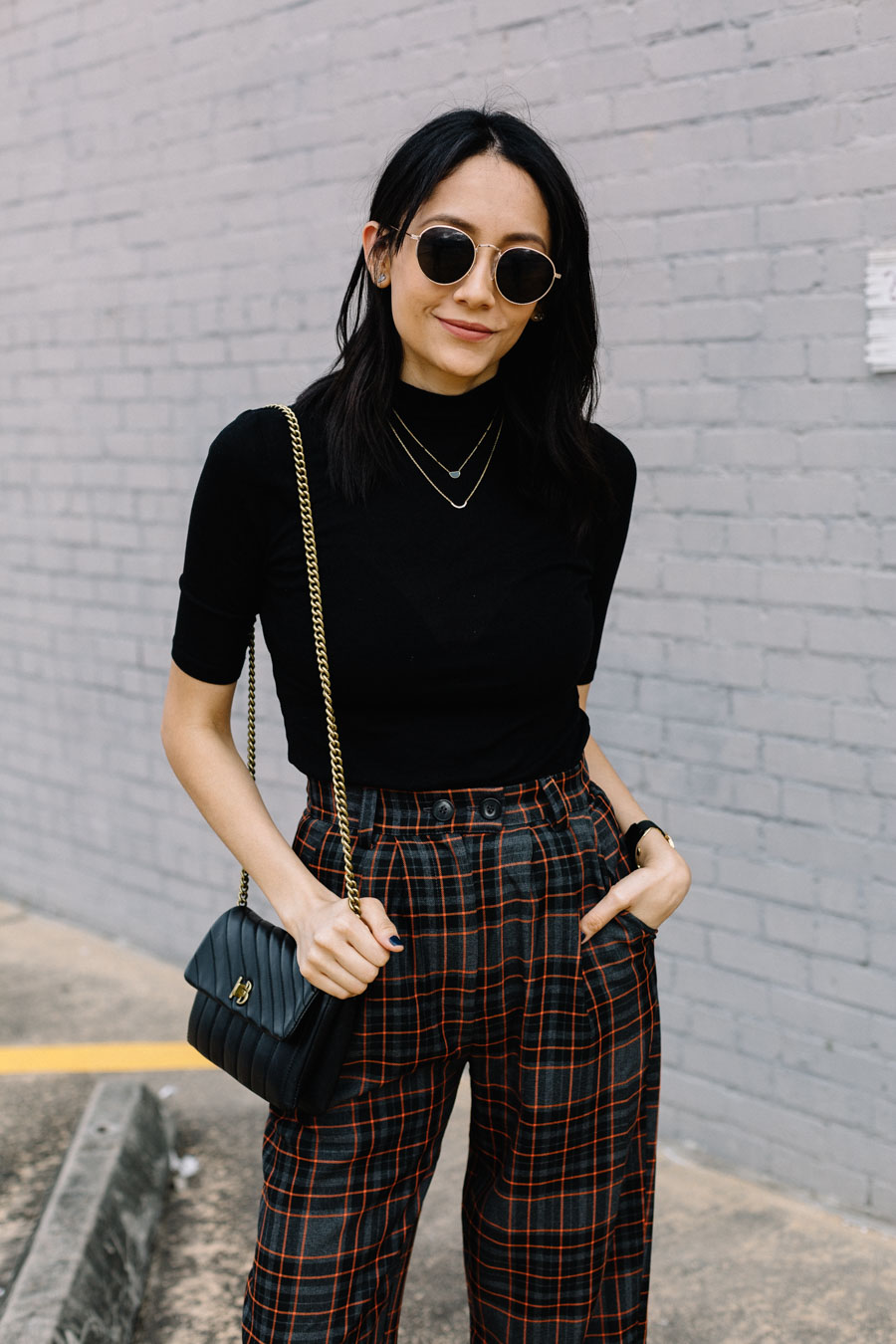 Lilly Beltran wearing Topshop check peg trousers with a black high neck top and Henri Bendel Bag for a casual street style look.