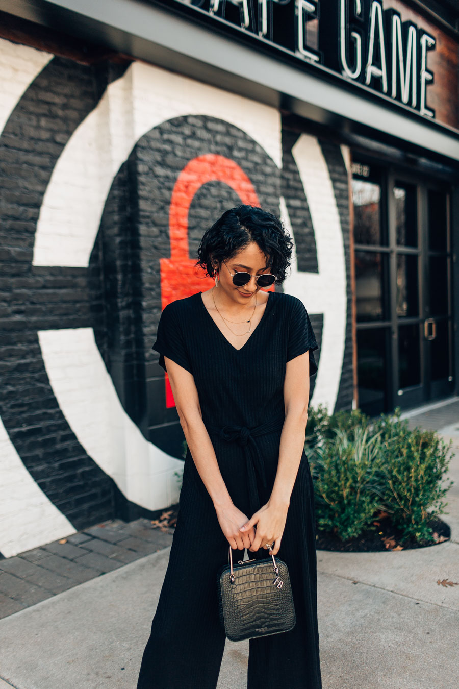Fashion Blogger Lilly Beltran styles a knit jumpsuit with Bauble Bar earrings, round sunglasses and Henri Bendel bag.