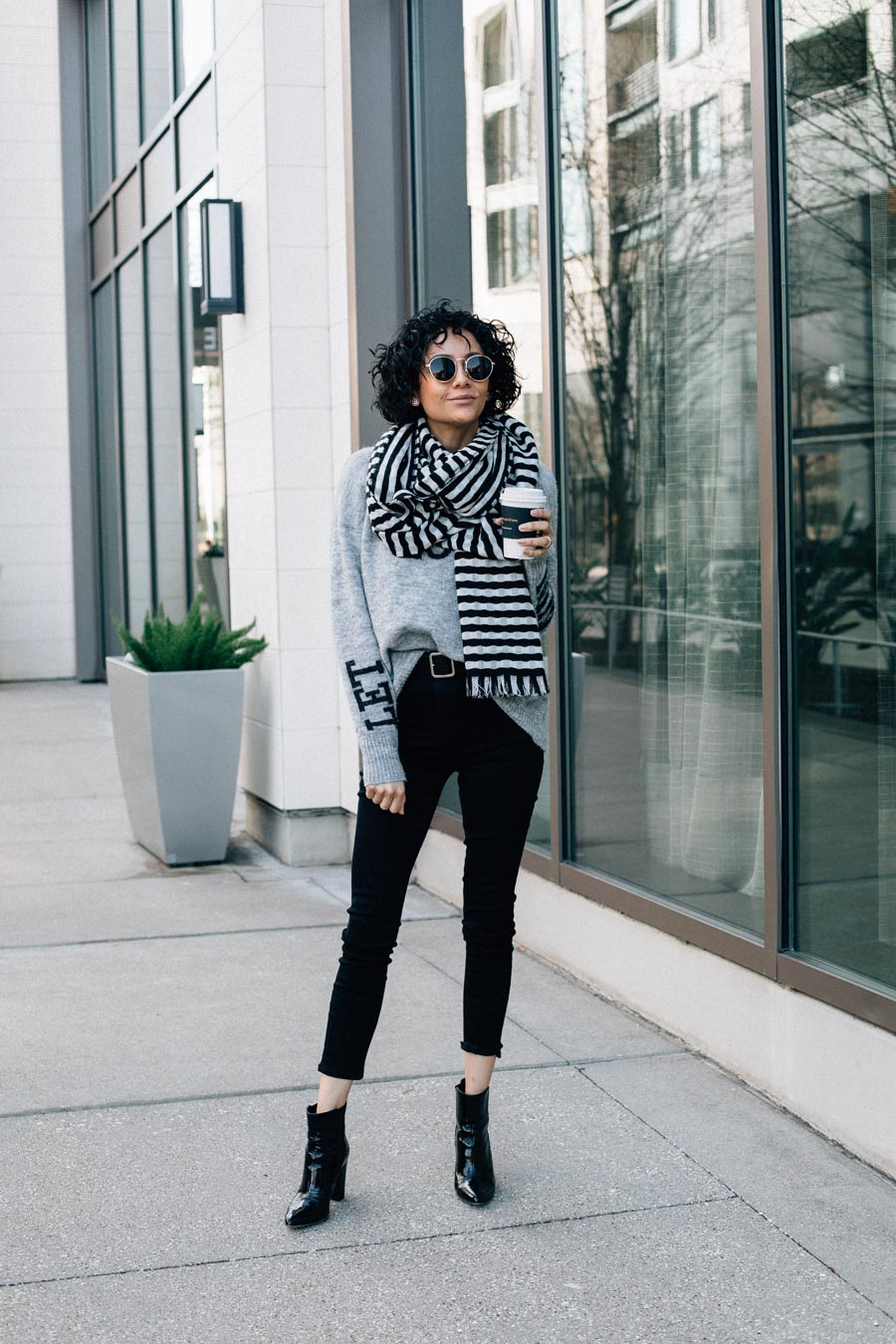 Casual and chic winter outfit idea. Black skinny Jeans, Grey Sweater, black ankle boots and striped scar.
