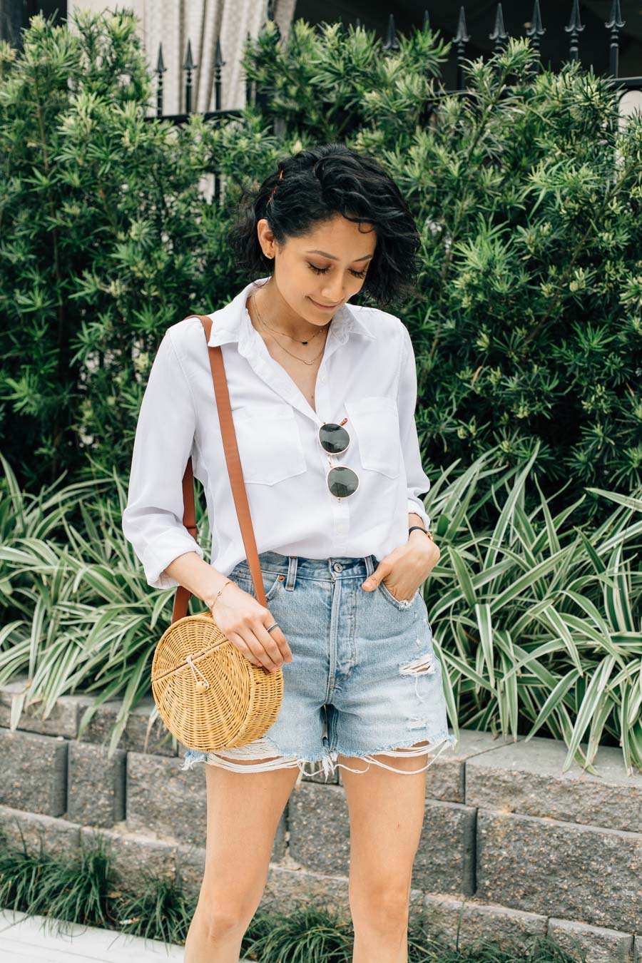 Fashion blogger Lilly Beltran styles Abercrombie denim shorts with J.Crew sandals and round wicker bag.