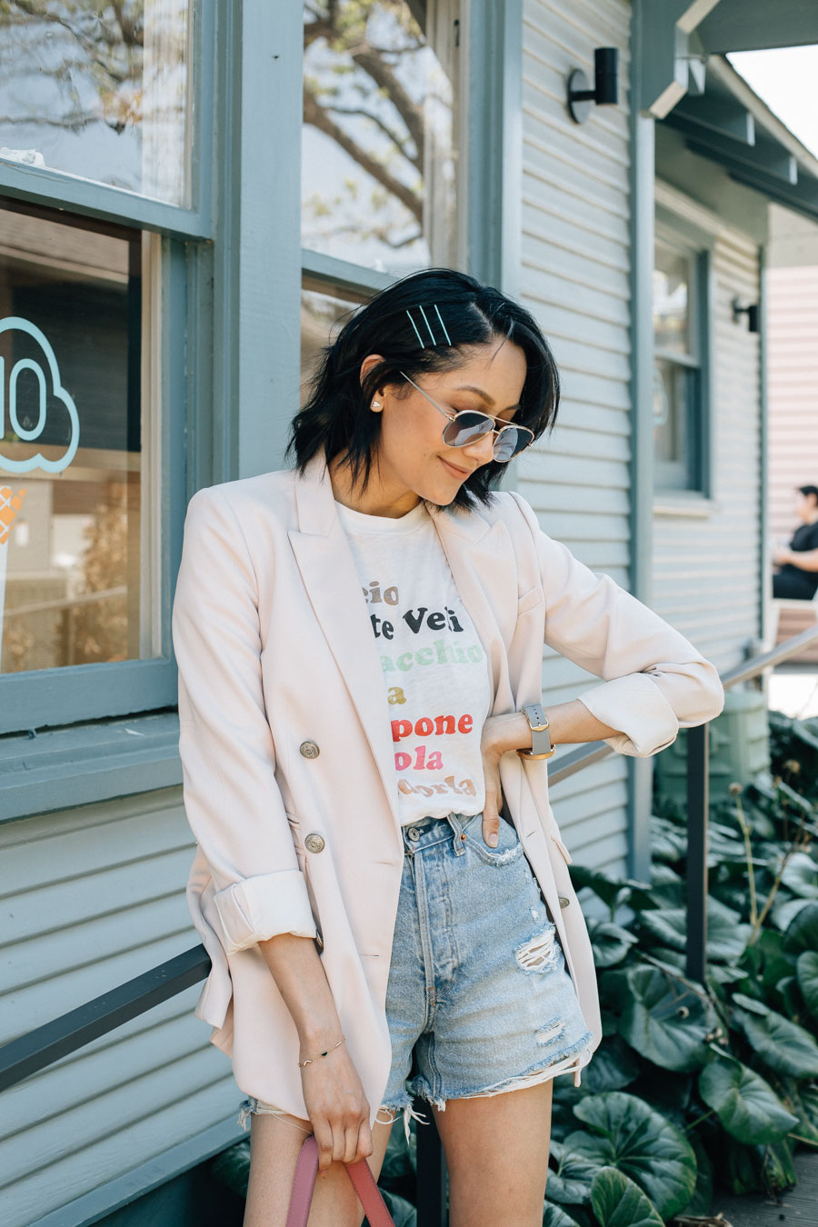Lilly Beltran wearing high waisted jean shorts with a graphic tee & blazer for an easy summer look