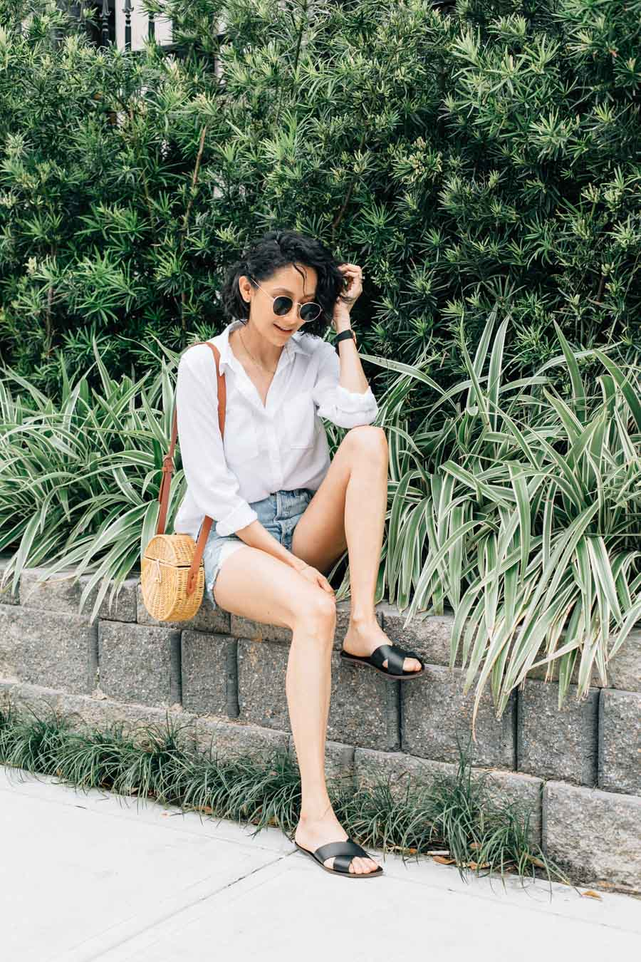 Lilly Beltran in a classic summer look with denim cutoffs, white button up shirt and round wicker bag.