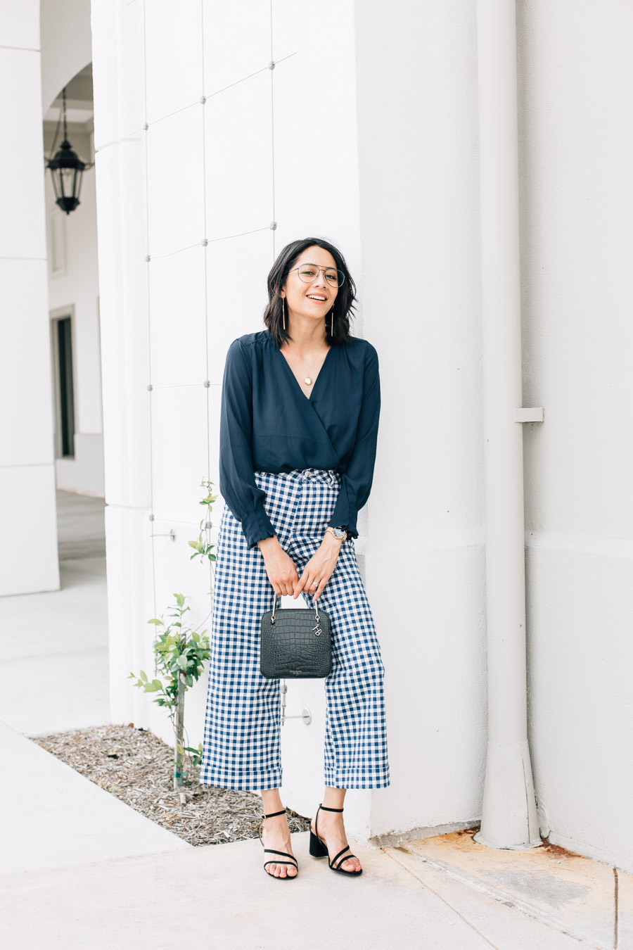 Lilly Beltran wearing wide leg gingham pants and navy wrap top for a chic office look + shares 10 bad habits you need to quit now.