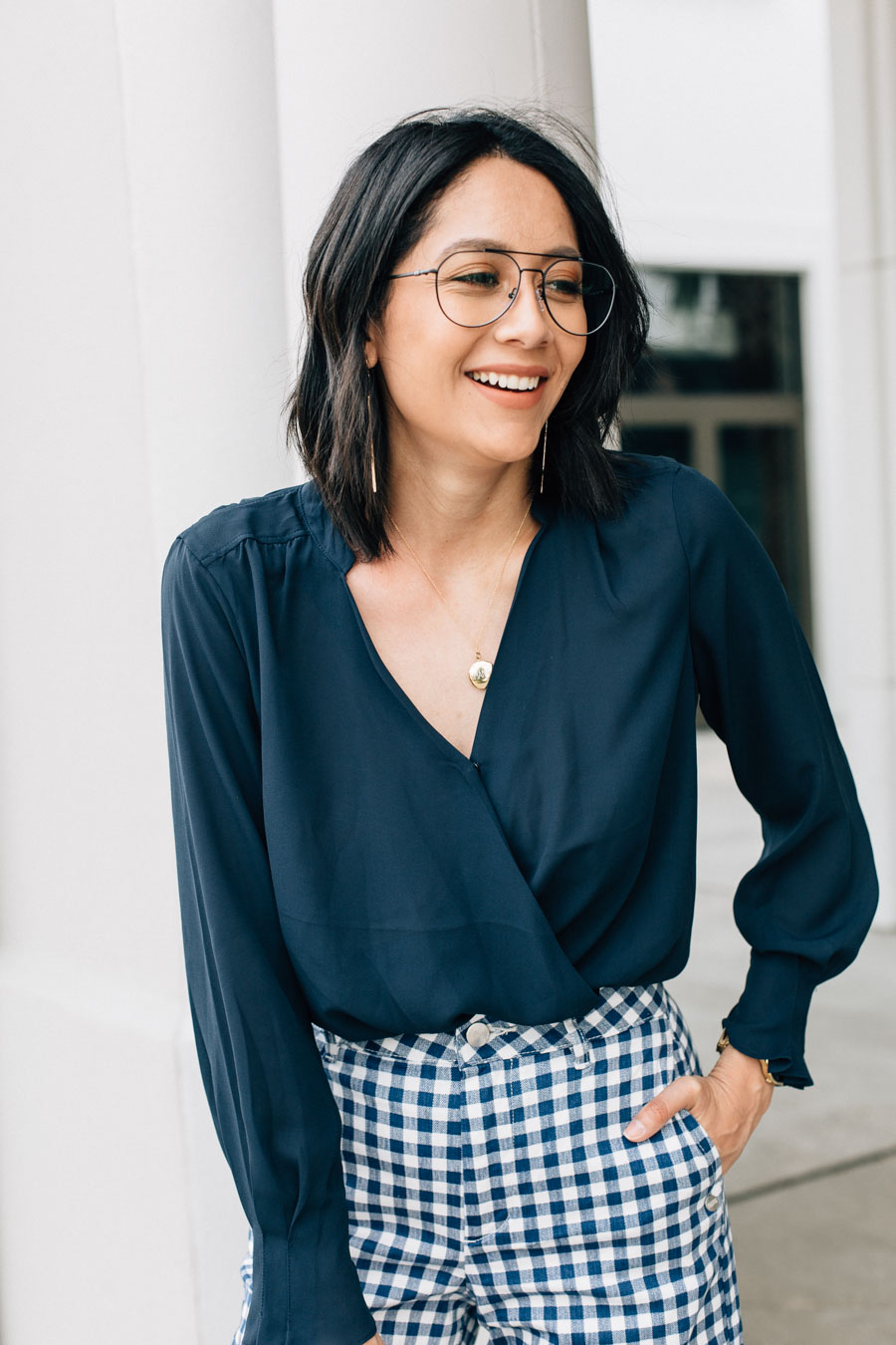 Lilly Beltran styles a Scotch & Soda wrap top with gingham pants and black naked sandals for a trendy office look.