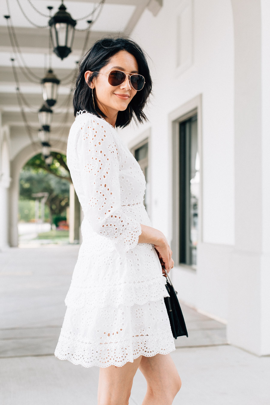 Fashion blogger Lilly Beltran wearing a white eyelet mini dress from Chicwish perfect for a summer date night.