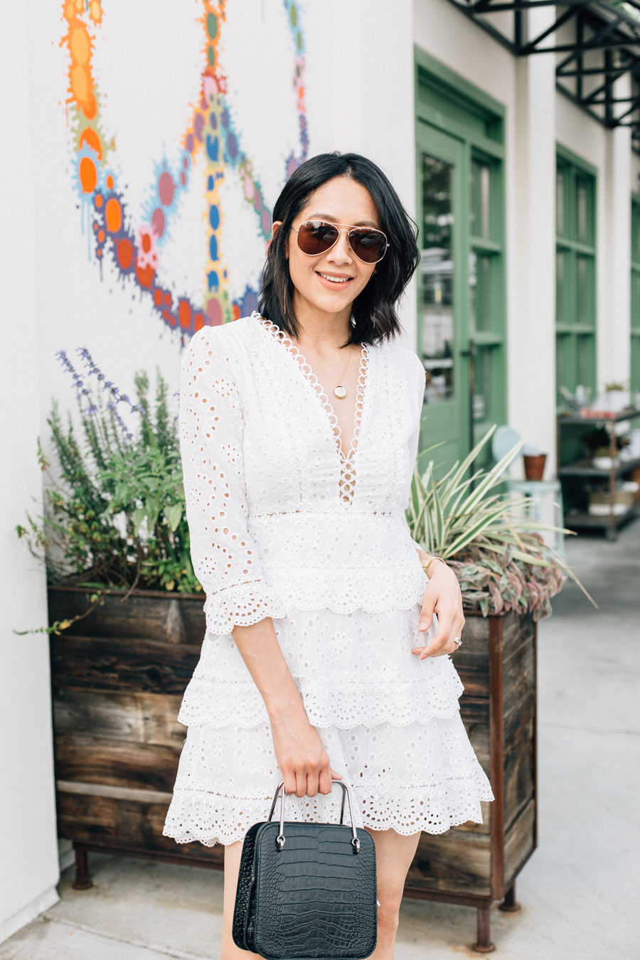 Lifestyle blogger Lilly Beltran wearing a white eyelet dress for a summer date night look.