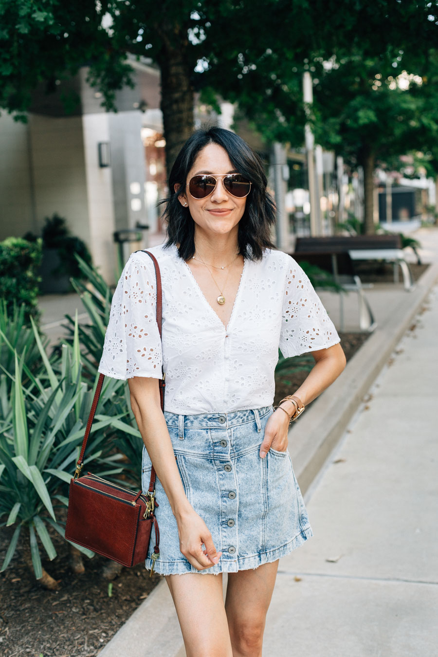 Lilly Beltran in a bell sleeve eyelet top from Abercrombie & button front denim skirt for a casual summer outfit