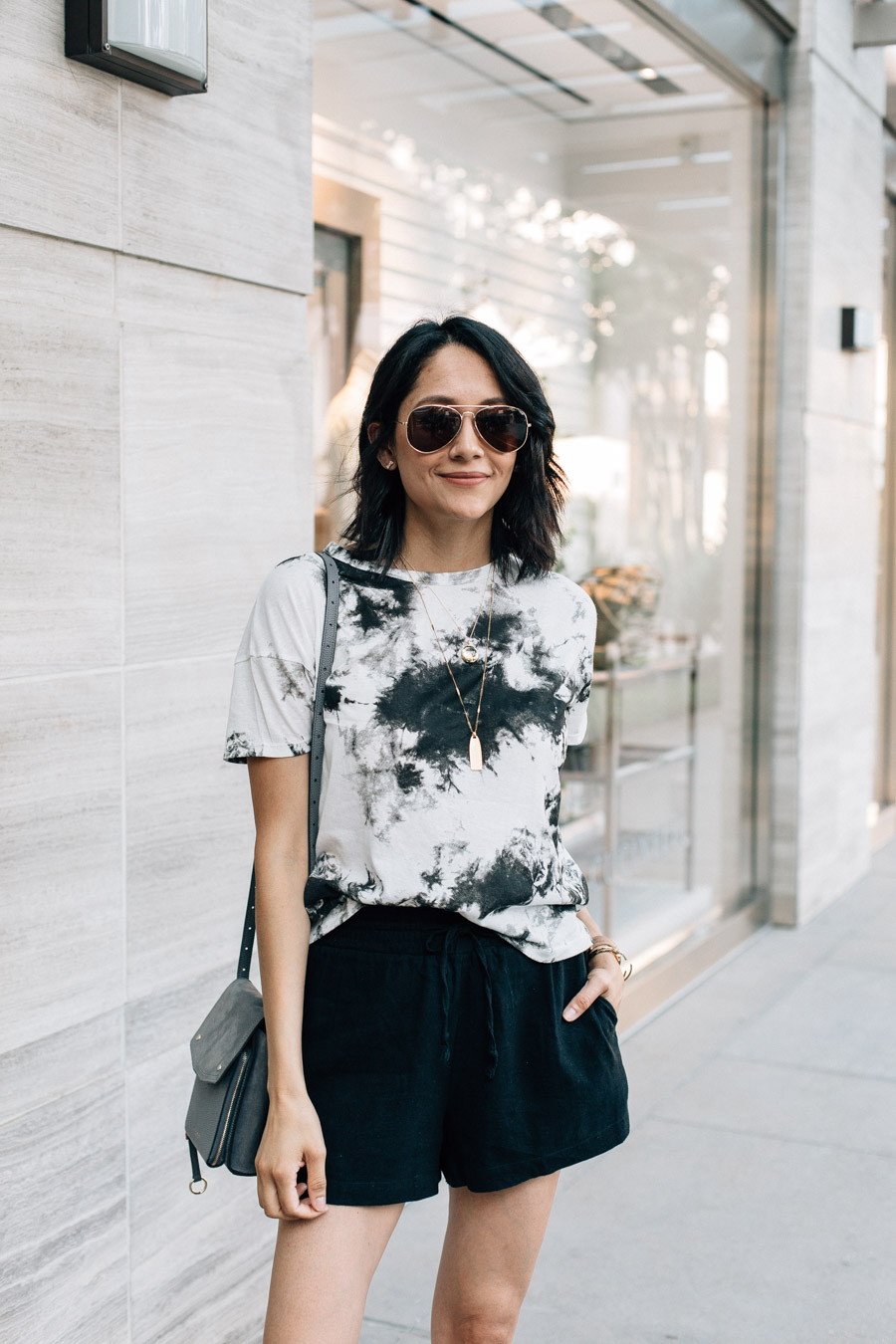 Fashion blogger Lilly Beltran wearing a black & white tie-dye shirt with black linen shorts and black slide sandals for a chic summer look