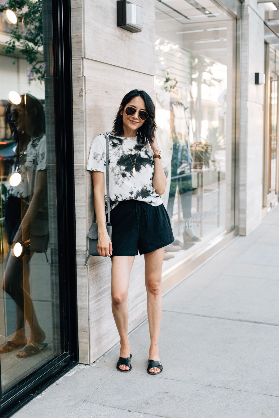 Hoe to wear the tie-dye trend as a neutral for summer | Black and white tie-dye shirt and black linen shorts.