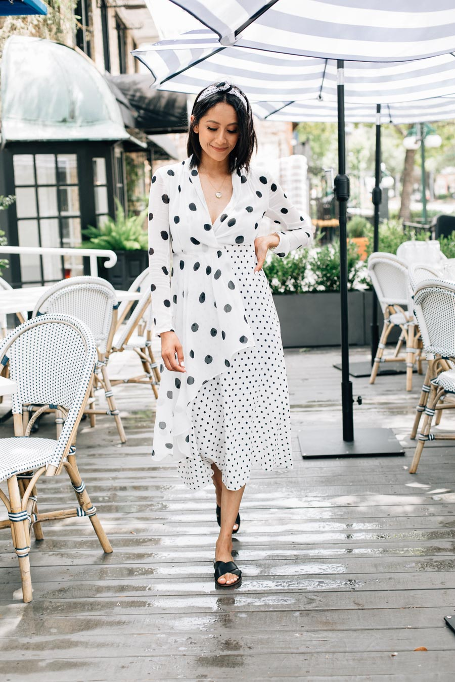 Lilly Beltran wearing a white and black polka dot dress from Farm Rio, with black sandals and a turban headband for a casual summer brunch look.