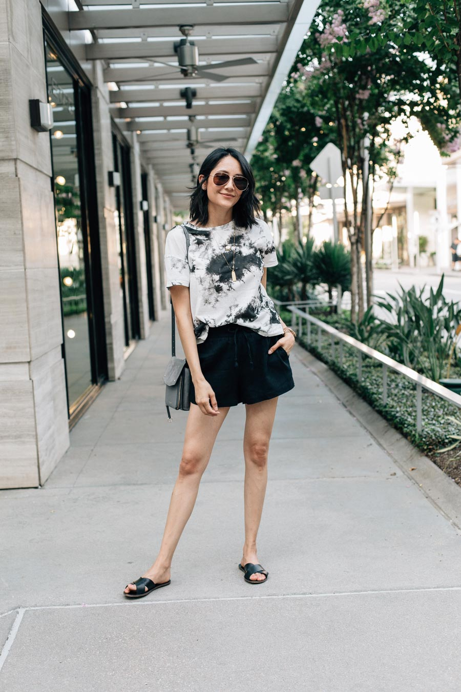 Lilly Beltran shows you how to wear the tie-dye trend as a neutral with a black and white tie-dye t-shirt and back linen shorts.