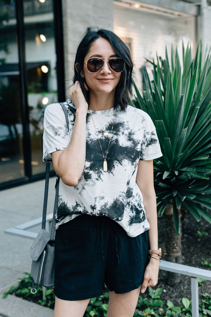 Lilly Beltran of Daily Craving Blog wearing a tie-dye t-shirt with black linen shorts for a trendy summer look