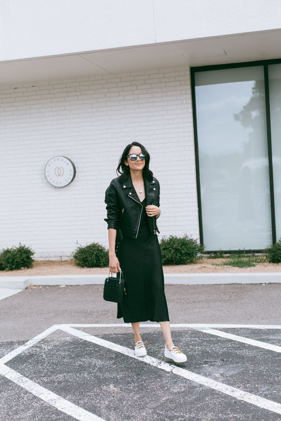 Fashion blogger Lilly Beltran styles a black slip dress with a leather jacket and white sneakers for a casual fall look.