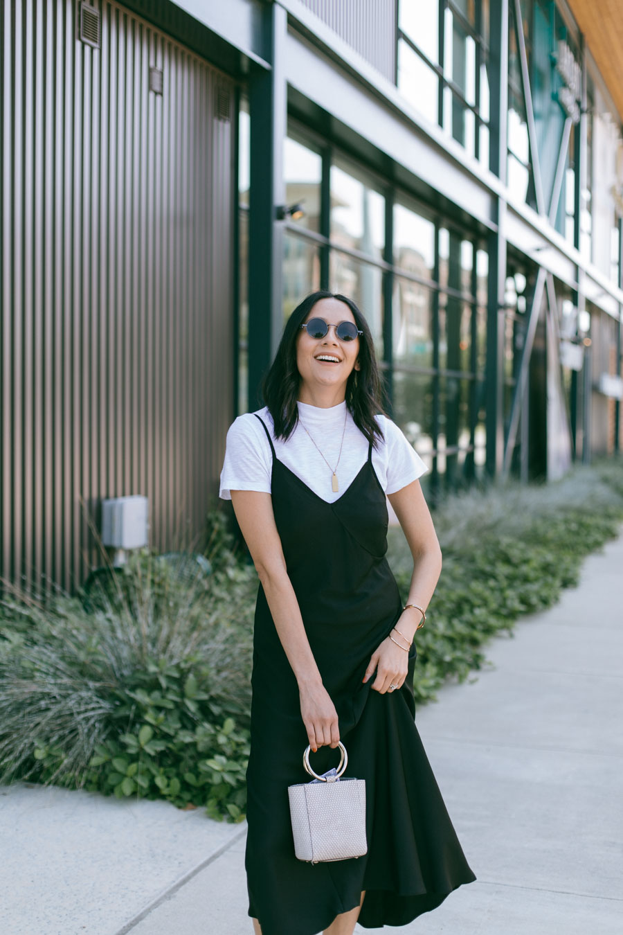 Lilly Beltran wearing a casual 90's inspired look with a black slip dress and white sneakers.