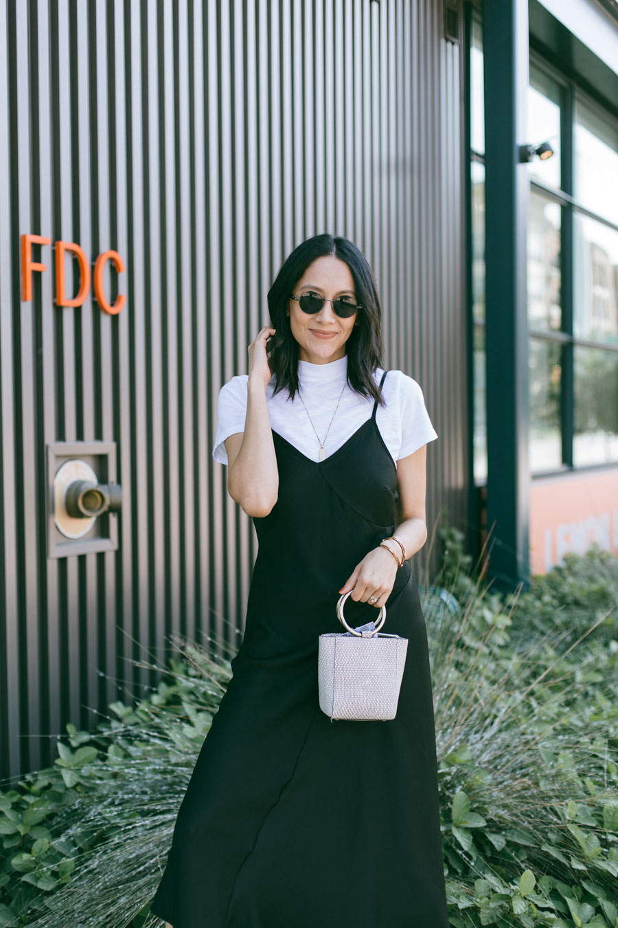 Style blogger Lilly Beltran wearing a black slip dress with a white t-shirt and white sneakers for a 90's inspired look.