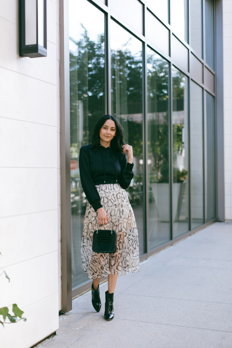 Lilly Beltran wearing a python print midi skirt with a black satin hoodie and black leather booties.