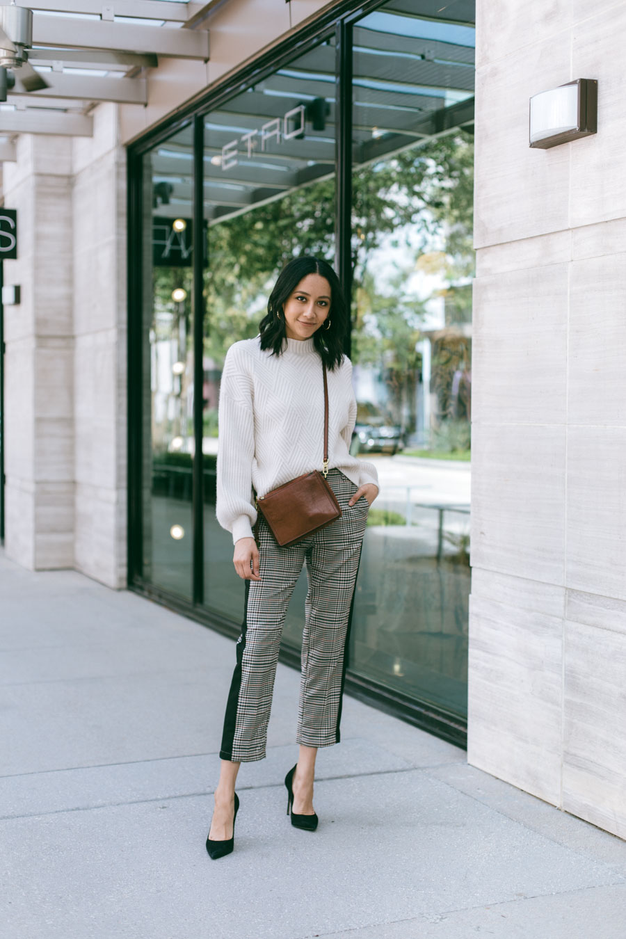 style blogger Lilly Beltran wearing brown trousers and a cream sweater with black pumps and brown leather bag for a fall outfit
