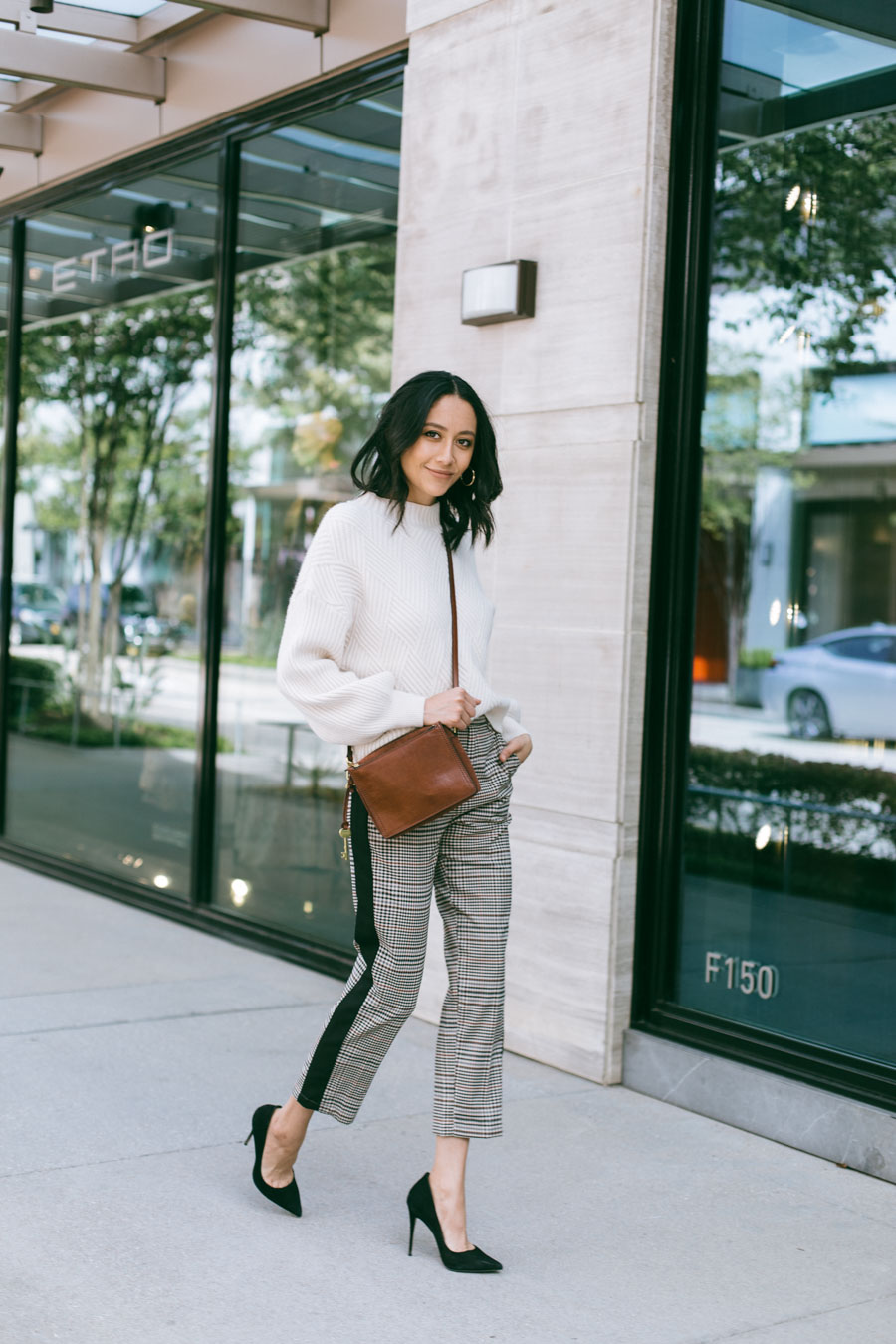 Fashion blogger Lilly Beltran wearing brown plaid pants with a cream mock neck sweater and black pumps for a chic fall outfit