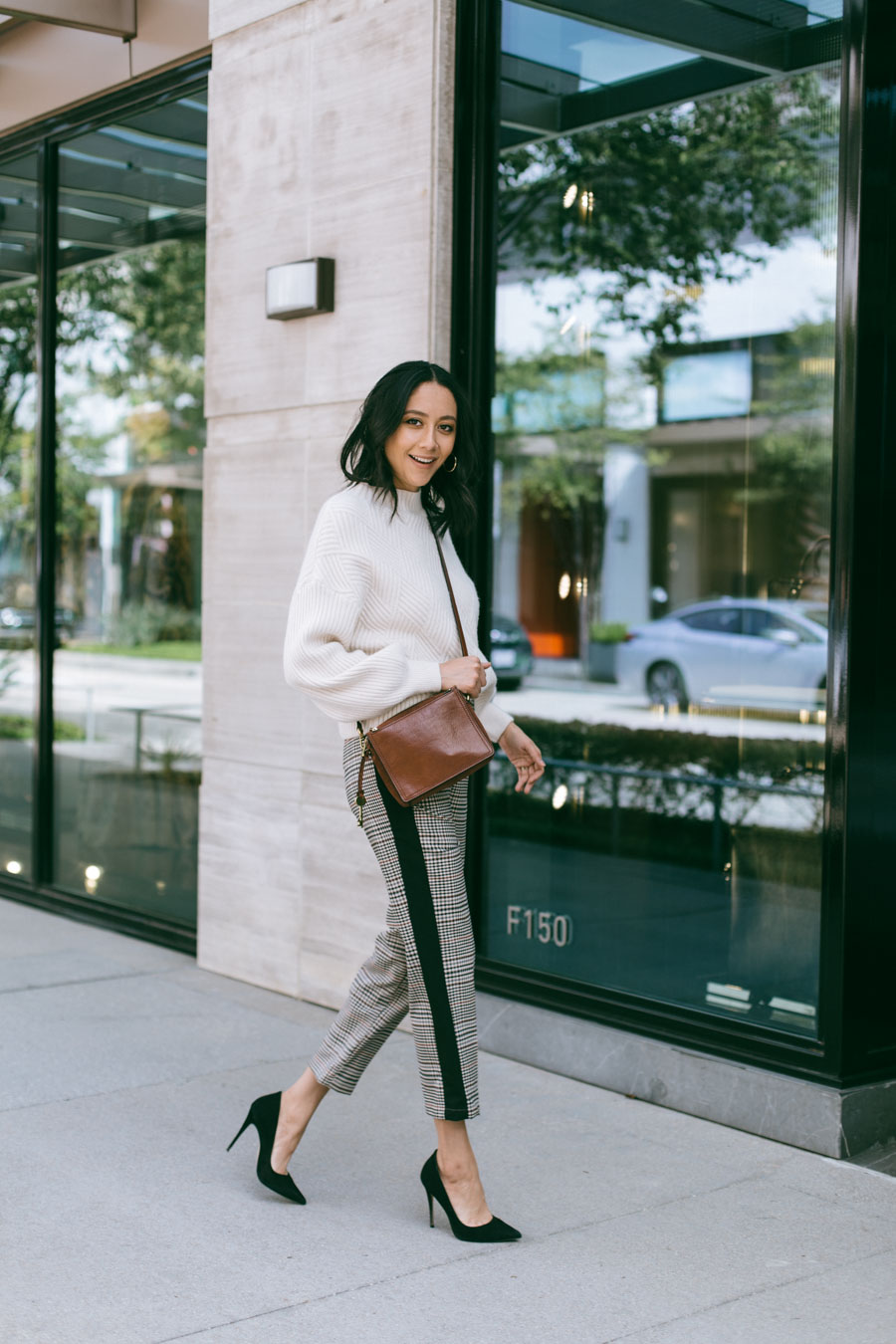 Street Style blogger Lilly Beltran wearing plaid trousers with a cream chunky sweater and black pumps for a chic thanksgiving outfit idea.