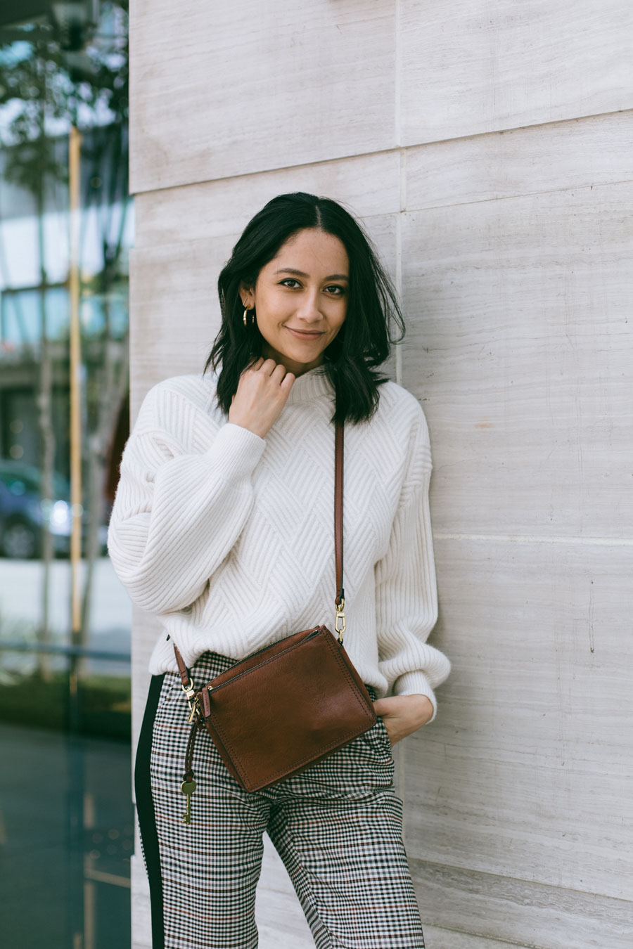 Blogger Lilly Beltran wearing a cream high neck sweater with trousers and a brown leather bag.