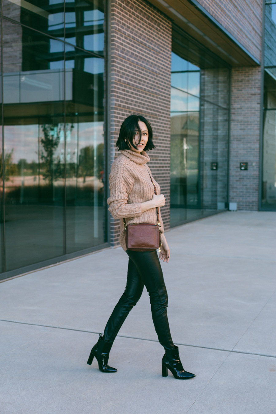 Street style blogger Lilly Beltran wears black leather leggings and oversized sweater.