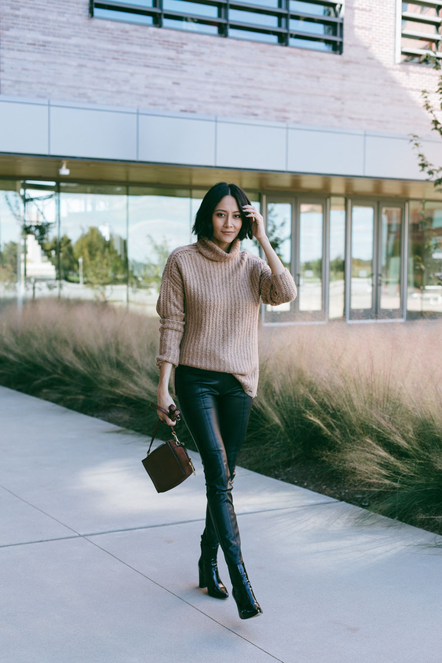 Lilly Beltran styles faux leather leggings with black boots and a chunky camel sweater.