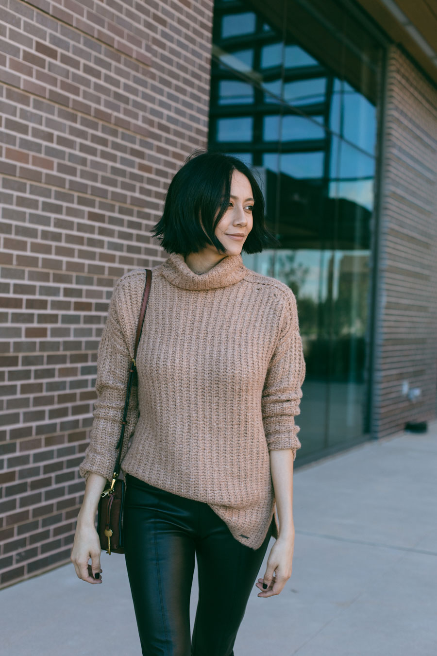 Style blogger Lilly Beltran wearing a tan chunky turtleneck sweater and faux leather pants for a chic fall outfit.