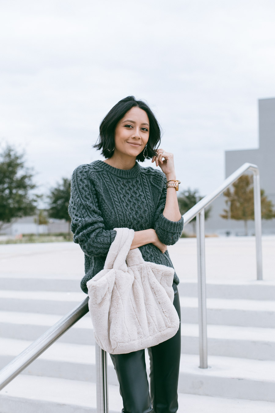 Fashion blogger Lilly Beltran in an easy fall outfit with black faux leather leggings and cable knit sweater.