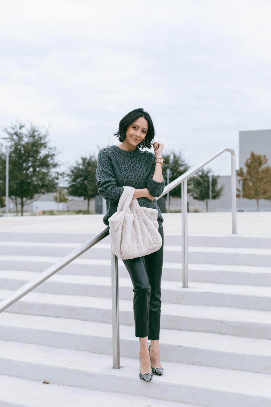 Lilly Beltran wearing faux leather pants with a cable knit sweater for an easy fall outfit.