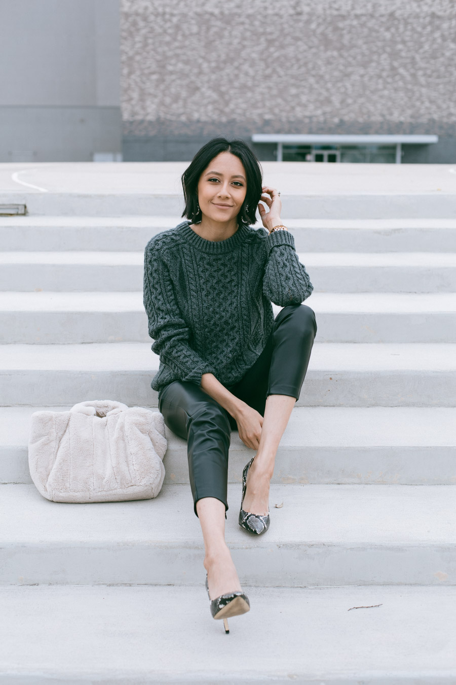 Lilly Beltran wearing a grey cable knit sweater and faux leather pants with sake print pumps.